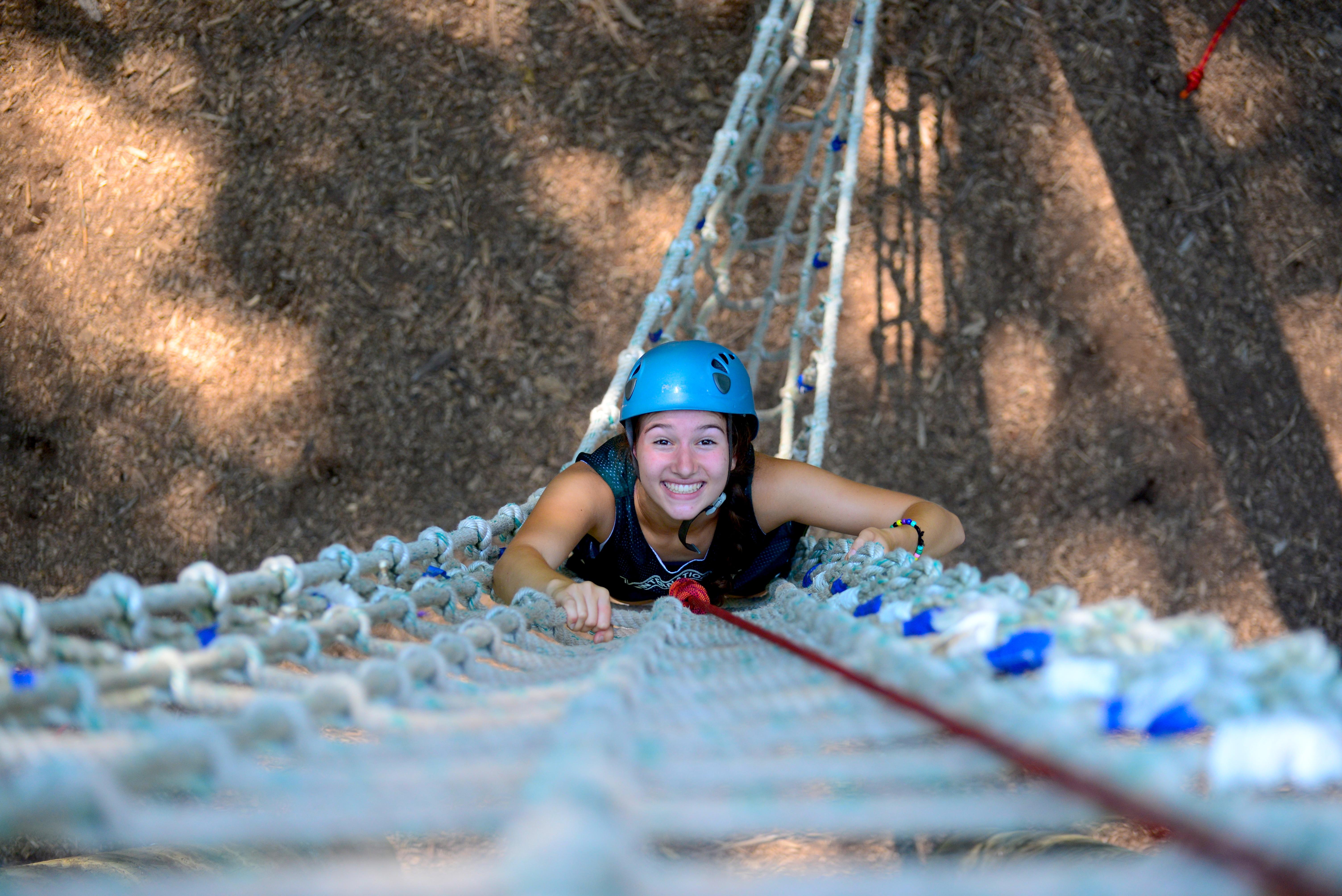 girl climbing up ropes course
