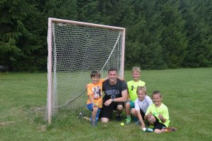camp counselor with kids at soccer field