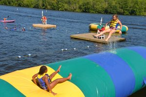 girls jumping on the blob at summer camp